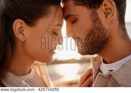 leisure, relationships and people concept - close up of happy couple with closed eyes on summer beach
