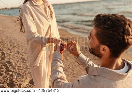 love and people concept - smiling young man with engagement ring making proposal to happy woman on beach