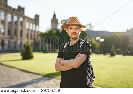 Cheerful Man Traveler In Hat And Backpack With European City Center Background. Travel And Old City