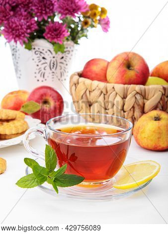 Tea with herbs fruits and cookies. Still life with hot drink apple and nuts at white wooden board in rustic style.