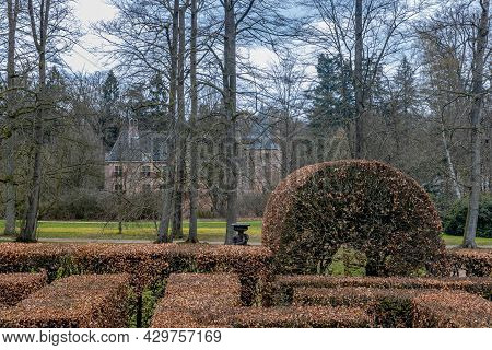 Part Of A Maze Made Up Of Brown Leaf Bushes With Bare Trees And The Het Oude Loo Castle In The Backg