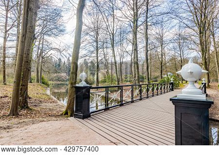 Wooden Footbridge Over A Stream, Decorative Balls On The Black Metal Railing And White Ironwork, Sur