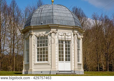 Tea Dome Or Theekoepel Or Gloriette With Its Square Windows And Gray Dome With Bare Trees In The Bac
