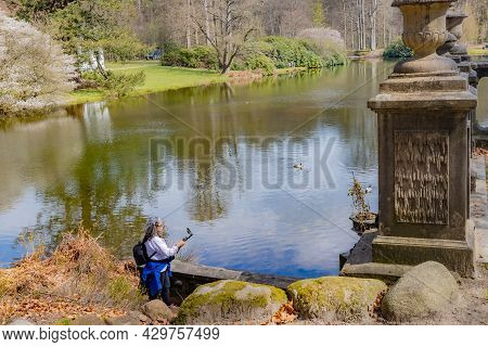 Lake With Reflection In The Water Surface With Mature Woman Filming With Her Mobile Phone Gimbal Tri