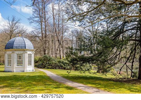 Field With A Dirt Trail, A Tea Dome Or Theekoepel Or Gloriette, Green Grass, Bare Trees And A Pond,