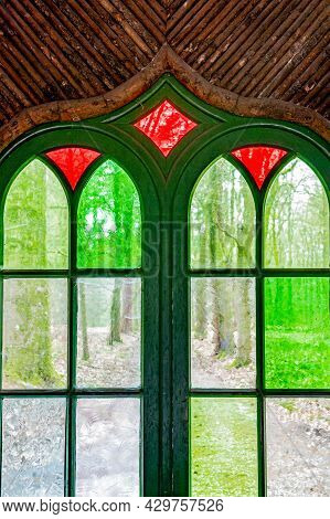 Close-up Of A Window With Wooden Frame, Green And Red Glasses, Seeing Through Them A Path And Trees,