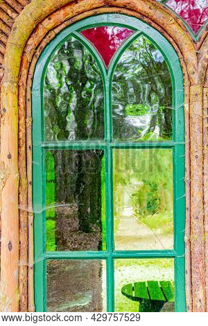 Window With A Wooden Frame, Green Glasses And A Red One, Seeing Through Them A Wooden Table, A Path