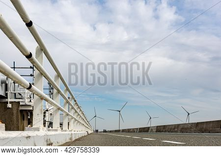 Road With Metal Railing And Windmills In The Background Next To Delta Works. Dams, Gates, Locks, Dik
