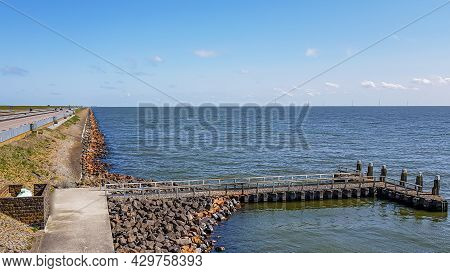 Small Jetty Between Stones With Part Of The Causeway At Afsluitdijk With The Lake Ijssel Created By