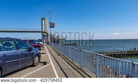 Ijsselmeer In The Netherlands. April 17, 2021. Cars Parked In Afsluitdijk, Stairs, A Bridge, Flags A