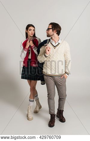 Woman Looking At Camera Near Man In White Knitted Pullover On Grey Background