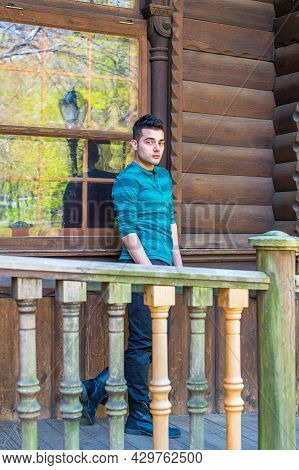 A Young Handsome Guy Is Standing By A Window Outside A Wooden House, Thoughtfully Looking At You. Sp