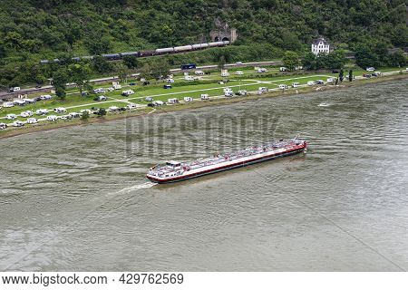 A Tanker Barge Sailing On The River Rhine In Western Germany, Visible Buildings And Caravans On The