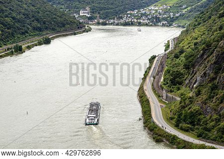 A Tanker Barge Sailing On The River Rhine In Western Germany, Visible Road And Railroad Tracks, Aeri