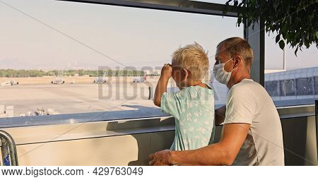 Father And Son Watching Airplanes At The Window In The Airport Waiting For Their Plane.