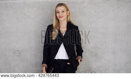 Self assured businesswoman near concrete wall