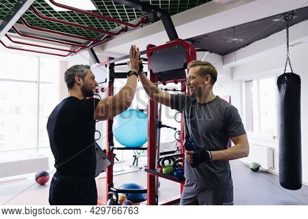 Fit Man Discussing Workout Plan With His Trainer, Personal Coach Before Starting Workout In The Gym.
