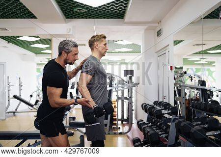 A Personal Trainer Motivates The Client To Lift Heavy Dumbbells In The Gym. Personal Workout Hour Wi
