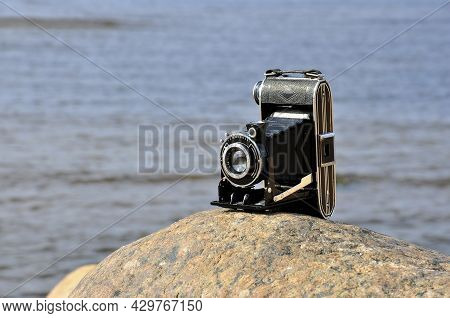 Black Vintage Analog Camera On The Background Of The Sea