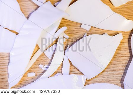 Close Up And Selective Focus On A White Plate Broken Into Small Pieces On A Wooden Table. Concept Of