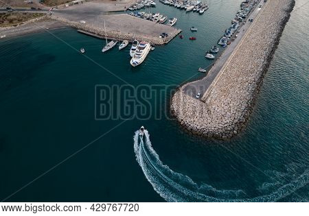 Aerial Drone View Of Speedboat Entering The Harbor Yachts Moored At The Marina. Latsi Harbor Paphos
