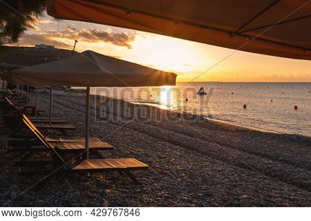 Beach Umbrellas And Relaxing Chairs At Sea At Sunrise. Empty Beach In The Morning Pissouri Cyprus