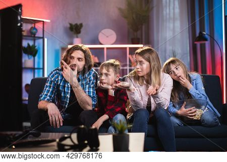 Unhappy Caucasian Family Of Four In Casual Wear Sitting On Couch And Feeling Bored While Watching Te