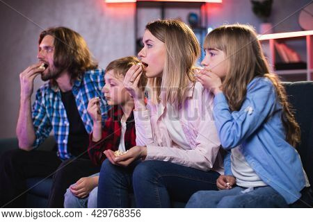 Astonished Parents With Little Son And Daughter Sitting On Couch With Open Mouth While Watching Exci