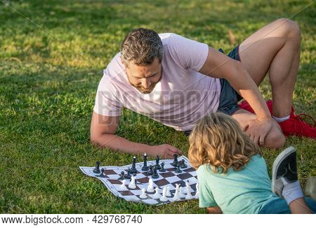 Spending Time Together. Strategic And Tactic. Tutorship. Dad And Child Play Logic Game.