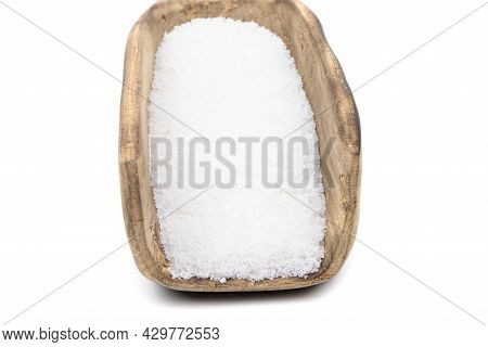 Salt In A Wooden Scoop Isolated On A White Background.