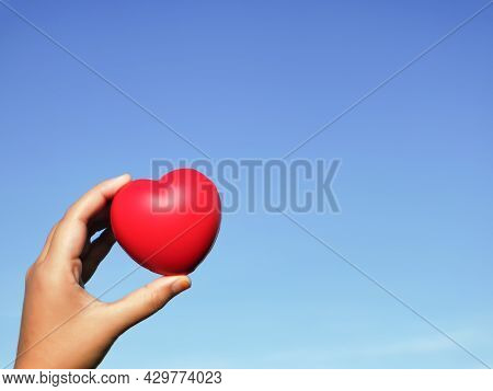 Blue Sky Background With Red Heart Shape In Hand. Love Concept. Selective Focus.