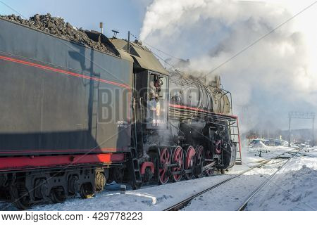 Sortavala, Russia - March 10, 2021: Locomotive Driver Looks Out Of The Booth Of The Old Soviet Steam