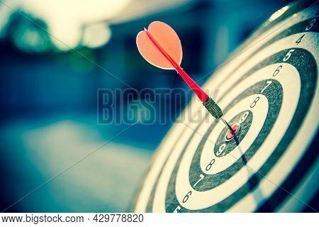 Bullseye Or Bulls Eye Target Or Dartboard Has Red Dart Arrow Throw Hitting The Center Of A Shooting