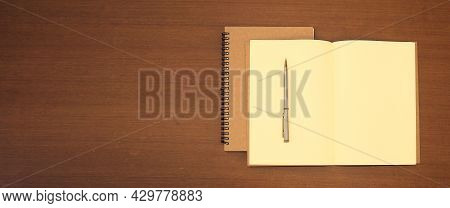 Close-up Notebook Or Note Book Diary With A Pen Or Pencil On Top View Wooden Desk Or Boardroom Table