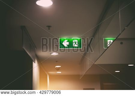 Green Emergency Fire Exit Sign Or Fire Escape On Ceiling For Doorway Or Door Exit In The Building Fo