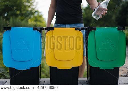 Close-up Of Human Hand Throwing Empty Glass Bottle In Recycling Bin. Tree Recycling Bins Outdoors. F