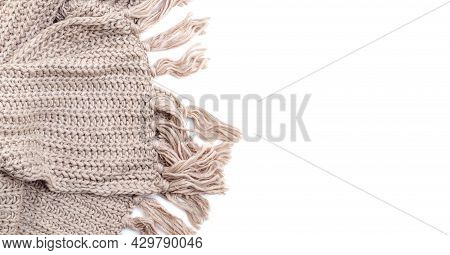 Part Of Beige Woolen Knitted Scarf With Tassels On White Background, Empty Place On Right.