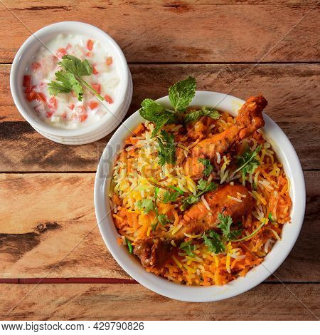 Traditional Hyderabadi Chicken Dhum Biryani Made Of Basmati Rice Cooked With Masala Spices, Served W