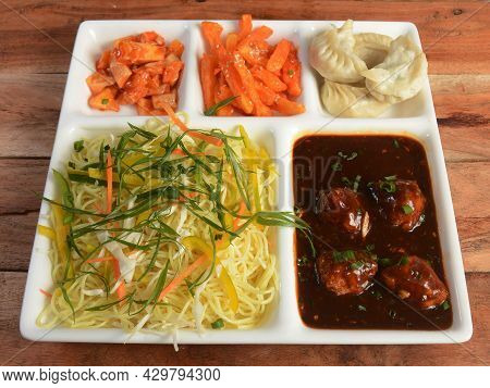 Chinese Veg Combo Meal - Consists Of Noodles, Manchurian, Fries, Veggies And Momos, Selective Focus