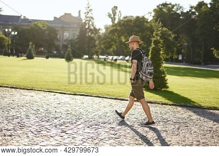Cute Male Traveler Wearing Backpack And Hat Going In European City Center Background. Travel, Wander