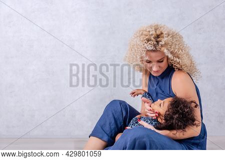 Caucasian Young Mother With Curls Hugs African American Girl. Happy Mixed Race Family Sitting On The