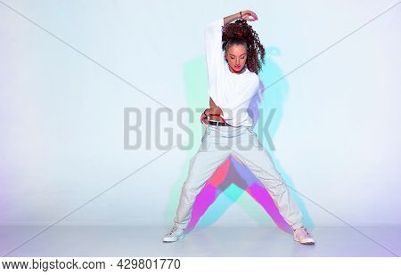 Dancing Mixed Race Young Girl In Colourful Studio Light. Stylish Female Dancer Performer Show Hip Ho