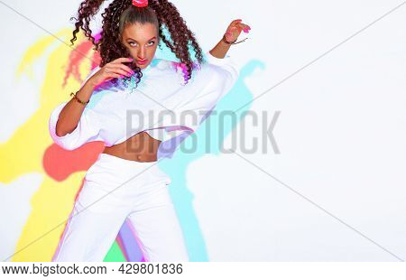 Beautiful Dancing Mixed Race Young Girl With Afro Hairs In Colourful Neon Studio Light On White Back