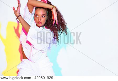 Modern Young Mixed Race Female With Afro Hairs Dancing In Colorful Light On White Background With Co