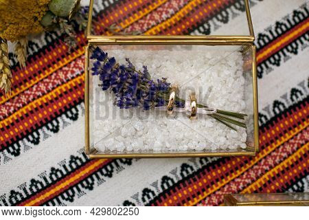 Gold Wedding Rings Of The Bride And Groom, Prepared For The Wedding Ceremony, Lie In A Glass Box Wit
