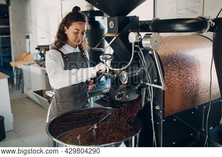 Coffee Cooling In Roaster Machine At Coffee Roasting Process. Young Woman Worker Barista Mixing Cool