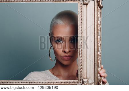 Millenial Young Woman With Short Blonde Hair Holds Gilded Picture Frame In Hands Behind Her Facial P