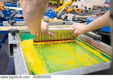 Serigraphy Silk Screen Print Process At Clothes Factory. Frame, Squeegee And Plastisol Color Paints.