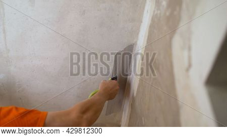 Master Is Applying White Putty On A Wall And Smearing By Putty Knife In A Room Of Renovating House I