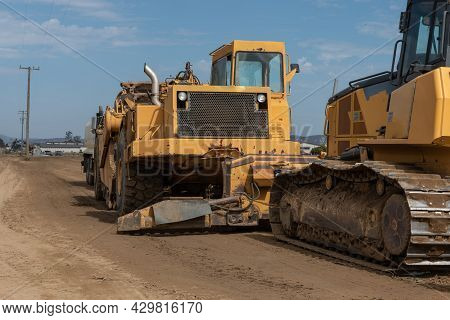 Heavy Grading Equipment Vehicles Lined Up On Open Dirt Field In California Farmland Ready For A Day